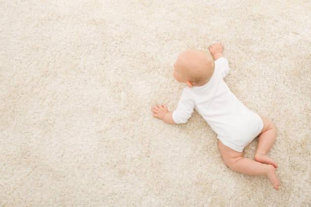 kruipende baby op tapijt achtergrond, kid bovenaanzicht, pasgeboren kind op beige deken - tapijt stockfoto's en -beelden