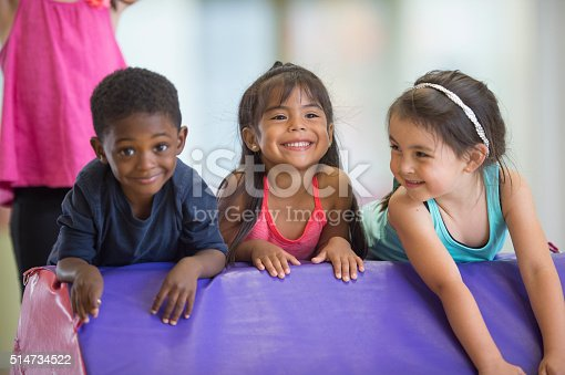 A multi-ethnic group of cute little kids are rolling on a mat together in gymnastics class.