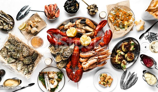 Crayfish and seafood table top view. Lobsters, crayfish, shrimps, clams, oysters, sushi. On a white tablecloth