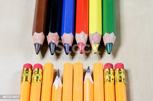 951081060 istock photo crayons and pencil sharpener on a wooden office table. Crayons with sharpening crayons and pencils on the table next to colored pencils. black background. 862320502