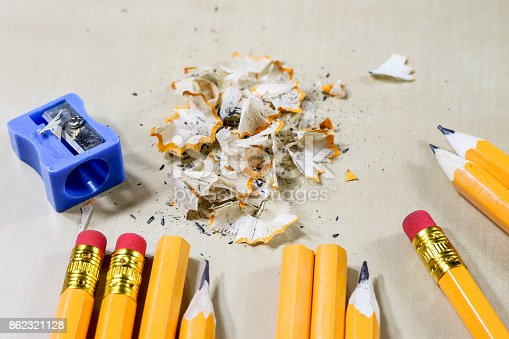 951081060 istock photo crayons and pencil sharpener on a wooden office table. Crayons with sharpening crayons and pencils on the table next to colored pencils. black background. 862321128