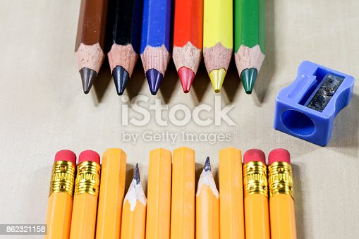 951081060 istock photo crayons and pencil sharpener on a wooden office table. Crayons with sharpening crayons and pencils on the table next to colored pencils. black background. 862321158