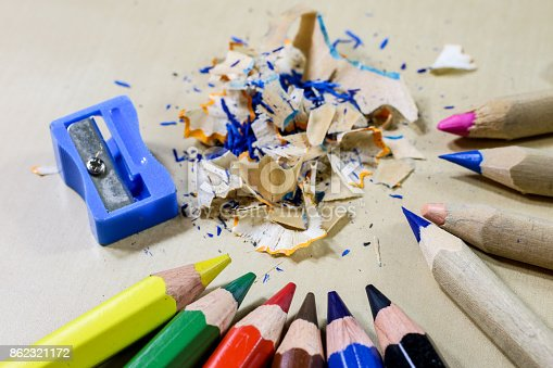 951081060 istock photo crayons and pencil sharpener on a wooden office table. Crayons with sharpening crayons and pencils on the table next to colored pencils. black background. 862321172