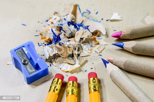951081060 istock photo crayons and pencil sharpener on a wooden office table. Crayons with sharpening crayons and pencils on the table next to colored pencils. black background. 862321706