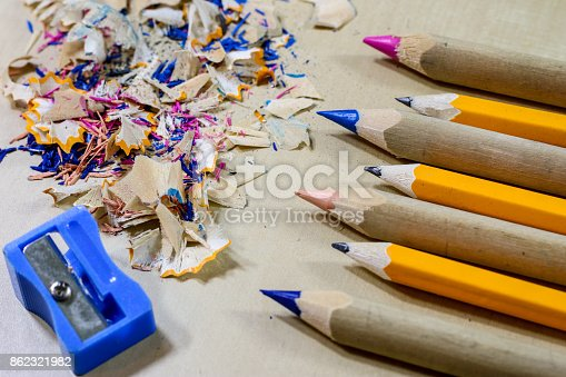 951081060 istock photo crayons and pencil sharpener on a wooden office table. Crayons with sharpening crayons and pencils on the table next to colored pencils. black background. 862321982