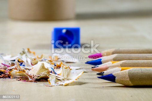 951081060 istock photo crayons and pencil sharpener on a wooden office table. Crayons with sharpening crayons and pencils on the table next to colored pencils. black background. 862322112