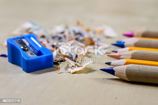 951081060 istock photo crayons and pencil sharpener on a wooden office table. Crayons with sharpening crayons and pencils on the table next to colored pencils. black background. 862322116