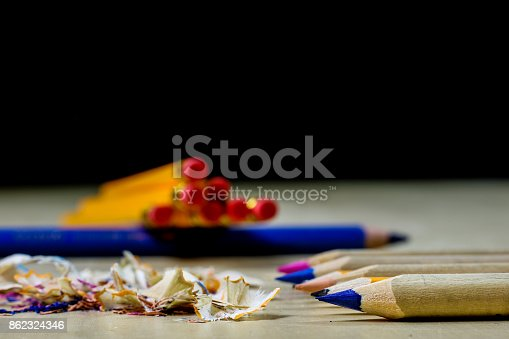 951081060 istock photo crayons and pencil sharpener on a wooden office table. Crayons with sharpening crayons and pencils on the table next to colored pencils. black background. 862324346