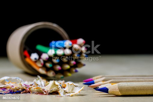 951081060 istock photo crayons and pencil sharpener on a wooden office table. Crayons with sharpening crayons and pencils on the table next to colored pencils. black background. 862324670
