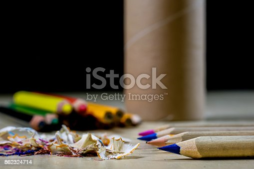 951081060 istock photo crayons and pencil sharpener on a wooden office table. Crayons with sharpening crayons and pencils on the table next to colored pencils. black background. 862324714