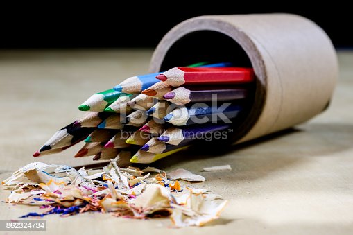 951081060 istock photo crayons and pencil sharpener on a wooden office table. Crayons with sharpening crayons and pencils on the table next to colored pencils. black background. 862324734