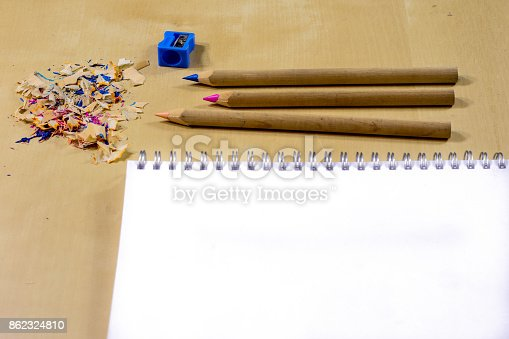 951081060 istock photo crayons and pencil sharpener on a wooden office table. Crayons with sharpening crayons and pencils on the table next to colored pencils. black background. 862324810