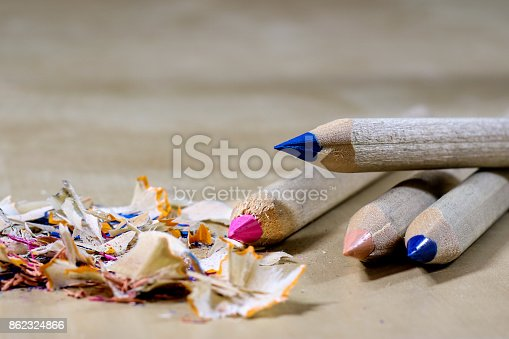 951081060 istock photo crayons and pencil sharpener on a wooden office table. Crayons with sharpening crayons and pencils on the table next to colored pencils. black background. 862324866