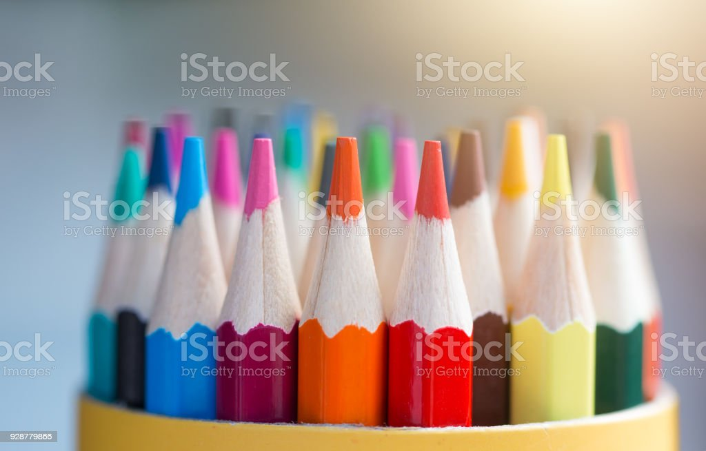 Crayons in a vase on a white background.