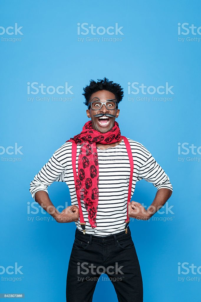 Crazy afro american guy in a french outfit Portrait of crazy afro american guy wearing striped long sleeved t-shirt, red suspenders and neckscarf, flexing his bicep and staring at camera with mouth open. Studio shot, blue background.  Adult Stock Photo
