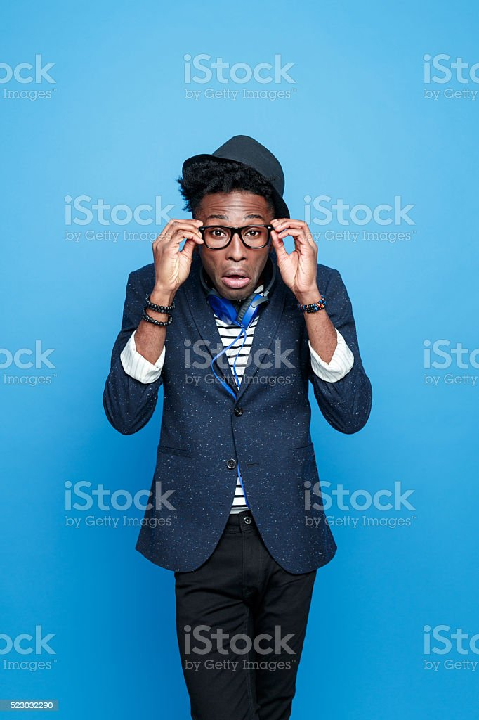 Crazy afro american guy in fashionable outfit Studio portrait of crazy, surprised afro american young man wearing striped top, navy blue jacket, nerd glasses, hat and headphone, looking at camera, making funny face. Studio portrait, blue background. Adult Stock Photo