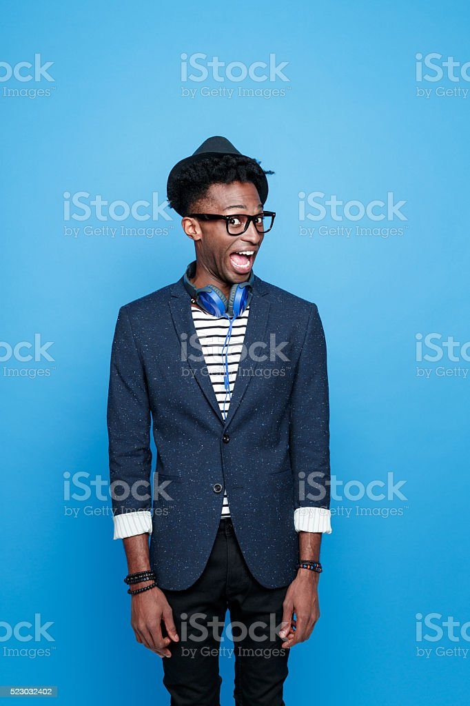 Crazy afro american guy in fashionable outfit Studio portrait of crazy afro american young man wearing striped top, navy blue jacket, nerd glasses, hat and headphone, looking at camera with mouth open. Studio portrait, blue background. Adult Stock Photo