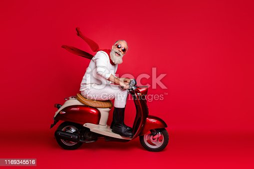 istock Crazy aged Santa man coming New Year 2020 party by vintage moped wear jumper and trousers isolated red background 1169345516
