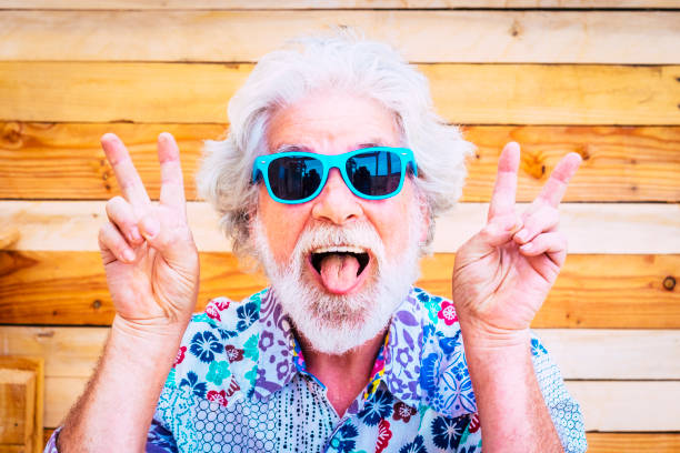 Crazy and happy active young and youth senior man making fun expression at the camera with winner hands - white hair and no limit age for old people love to play - happiness lifestyle for mature retired stock photo