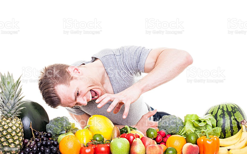 Crazy athletic man with fruits and vegetables, isolated on white stock photo