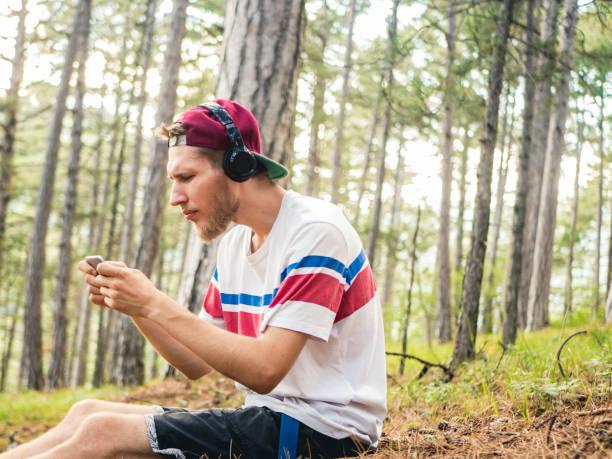 クレイジーひげを生やしたカジュアル ヒップとキャップに座っている携帯電話とヘッドフォンのスマート フォンでゲームを遊ぶと自然の森 - ゲーム ヘッドフォン ストックフォトと画像