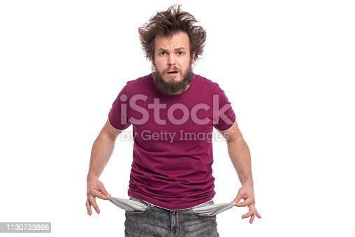 Crazy bearded Man with funny Haircut showing his empty pockets, turning his pockets inside out. Portrait of sad Guy, isolated on white background. Unhappy face expression. Money concept.