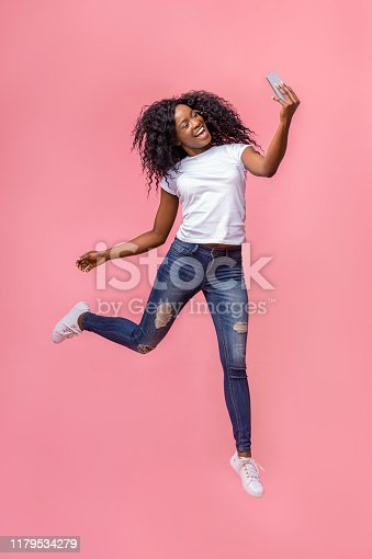istock Crazy black girl making selfie while jumping in the air 1179534279