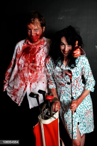 Bloodied retro husband and wife holding golf clubs. Wife look crazy while huband tries to be cool