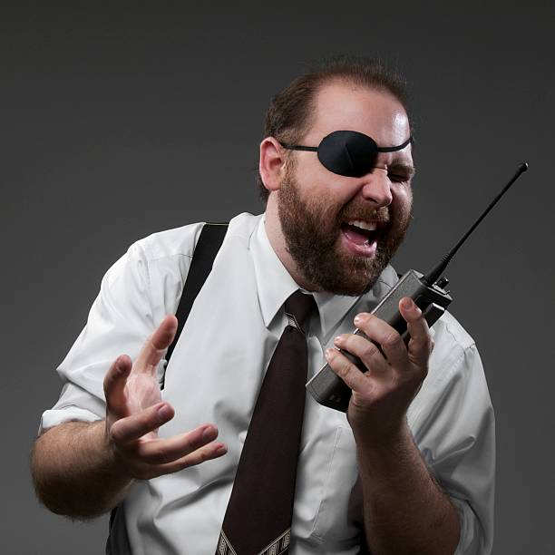 Crazy Business Man Crazy man in suspenders talking on walkie-talkie costume eye patch stock pictures, royalty-free photos & images
