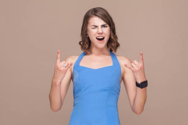verrückte geschäftsfrau demonstrieren rock'n'roll zeichen. - rock n roll kleider stock-fotos und bilder