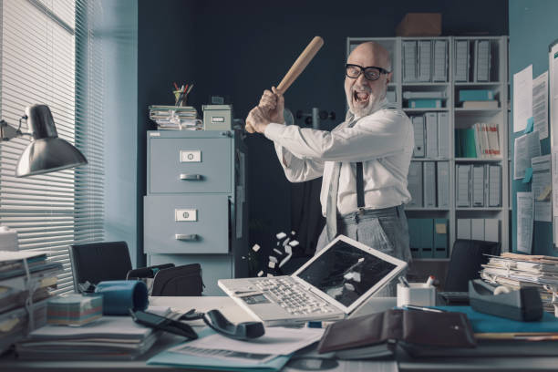 Crazy businessman destryoing his office with a baseball bat stock photo