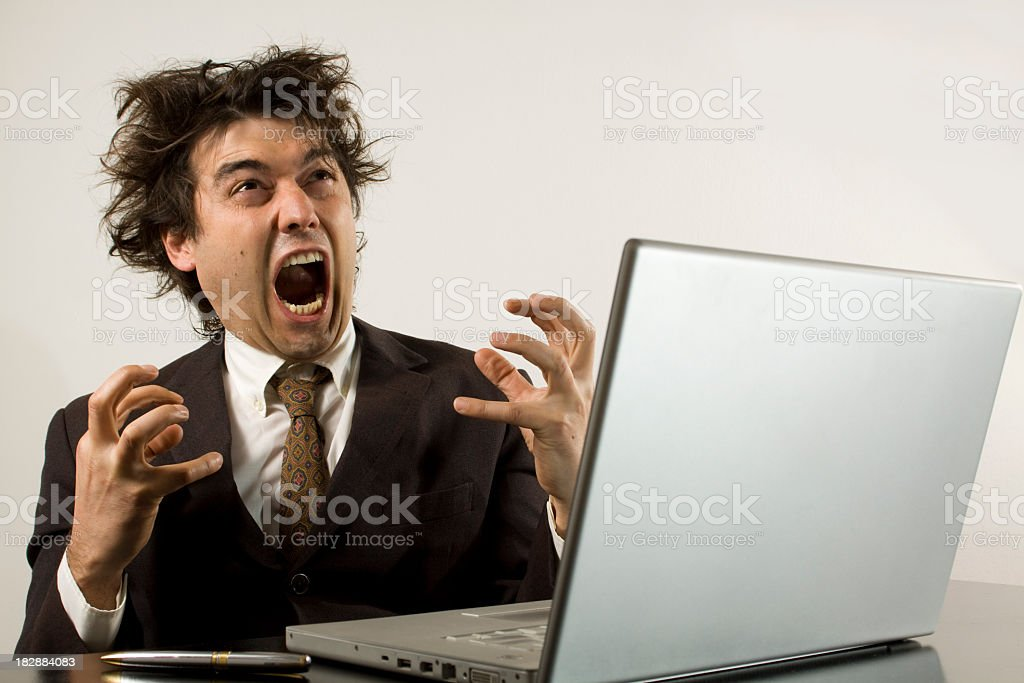 Crazy businessman frustrated with his computer stock photo