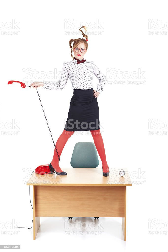 Crazy businesswoman standing on office desk and spining telephone earphone royalty-free stock photo