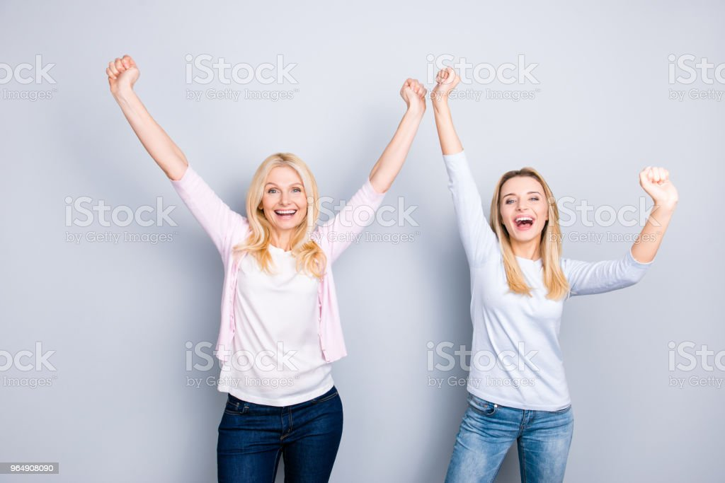 Crazy cheerful funky positive mother and daughter holding hands up chilling dancing celebrating victory laughing enjoying good news wearing jeans isolated on grey background royalty-free stock photo