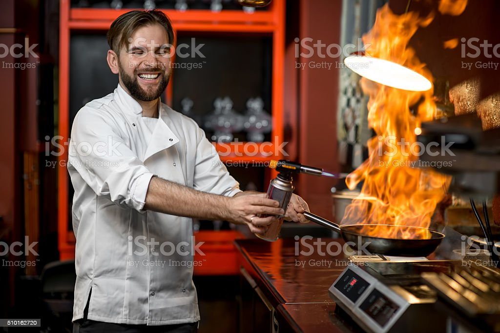 Crazy chef cooking with big fire on the frying pan stock photo