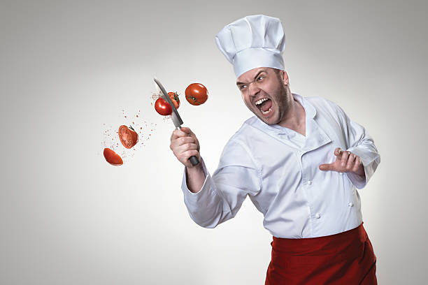 Crazy chef Portrait of a  chef with a knife in his hand,  to beat tomato kitchen knife stock pictures, royalty-free photos & images