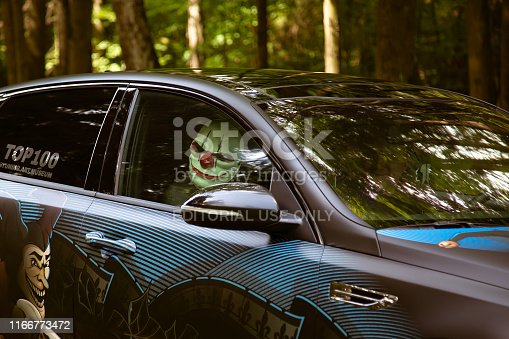 istock Crazy clown inside a tuned car in the forest. 1166773472