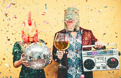istock Crazy couple celebrating new year eve wearing chicken and dinosaur t-rex mask - Young trendy people having fun drinking champagne and listening music with vintage boombox - Absurd and holidays concept 1201208190