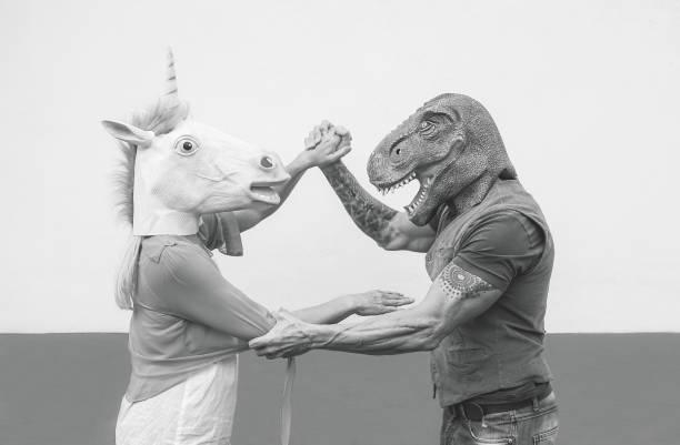 verrücktes paar tanzen und tragen dinosaurier und einhorn maske - senior trendige leute, die spaß am karnevalsumzug maskiert - absurd, exzentrisch, surreal, fest und lustige maskerade-konzept - coole halloween kostüme stock-fotos und bilder