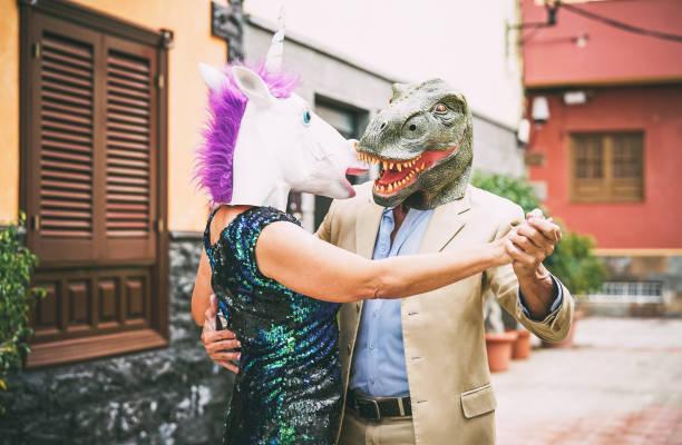 verrücktes paar tanzen und tragen dinosaurier t-rex und einhorn maske - senior eleganten menschen, die spaß am karnevalsumzug maskiert - absurd, exzentrisch, surreal, fest und lustige maskerade-konzept - coole halloween kostüme stock-fotos und bilder