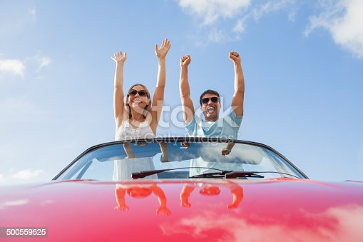 Crazy couple standing in red cabriolet on a sunny day