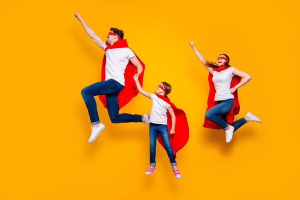 crazy pappa mamma och foxy dotter flyttar upp luft höja knytnävar bär superhjälte uddar isolerad gul bakgrund - superwoman barn bildbanksfoton och bilder