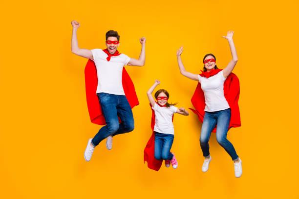 crazy daddy mamma och foxy dotter hoppar högt slitage tecknad superhjälte slängar isolerad gul bakgrund - superwoman barn bildbanksfoton och bilder