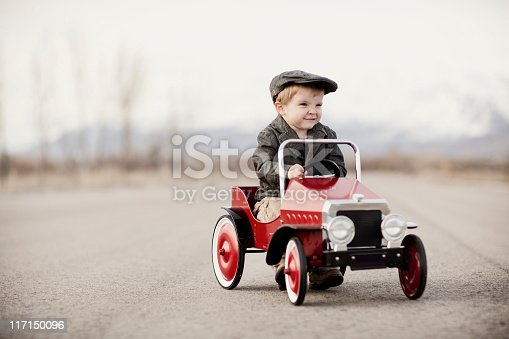 Look out! A young boy driver is out for a drive in his pedal car. Vintage black and white.