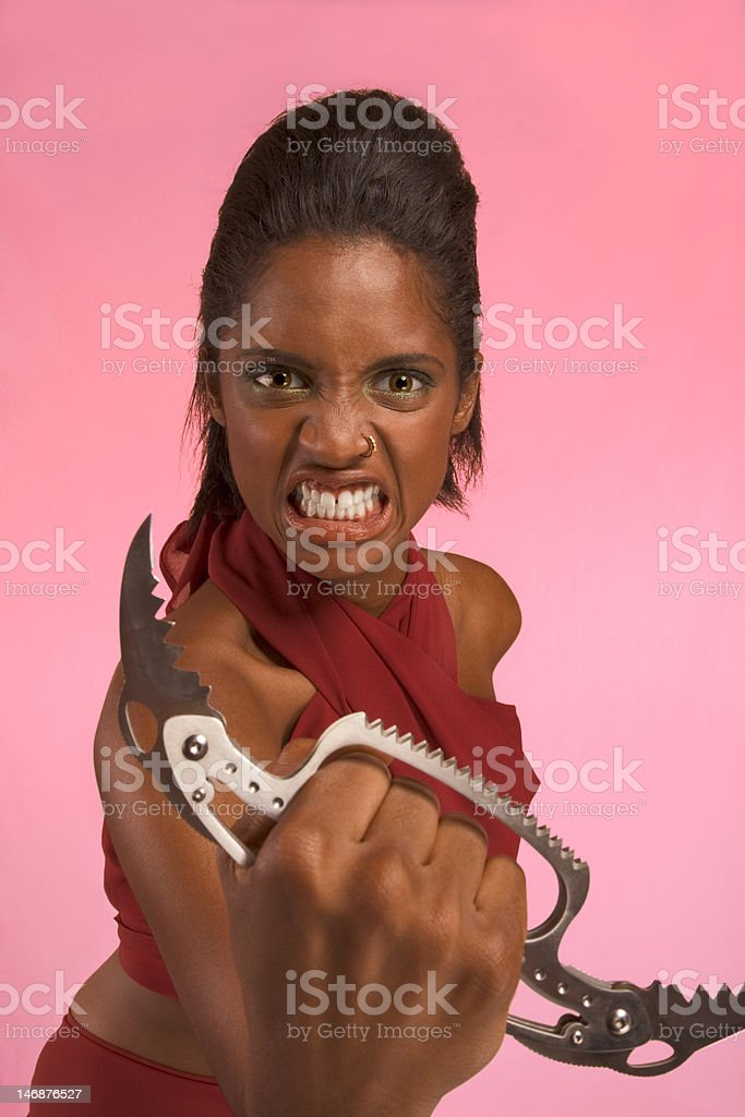 Crazy ethnic woman threatens using Brass Knuckle knife royalty-free stock photo