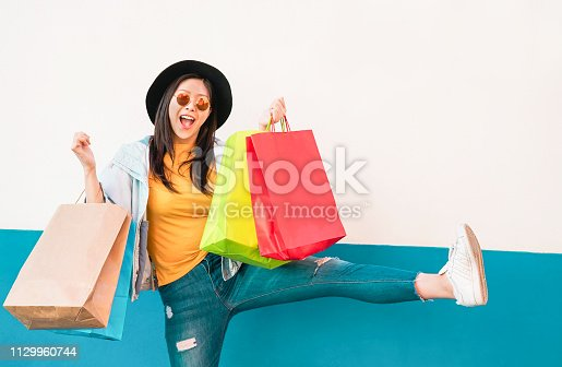 Crazy fashion Asian girl doing shopping in mall center - Happy Chinese woman having fun buying new clothes - Consumerism, people and youth lifestyle concept