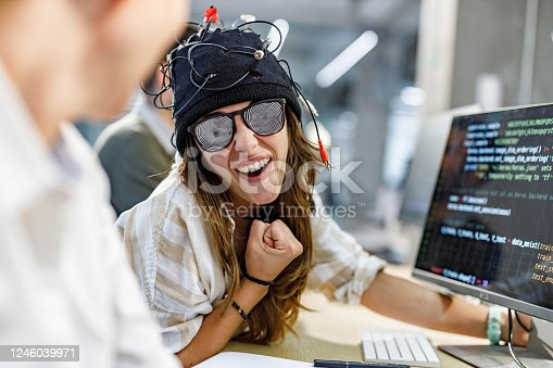 Crazy female programmer having fun while being under the influence of manipulation in the office.