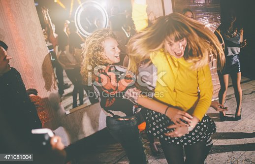 Female friends dancing wildly on the dance floor at a night club