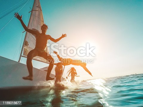 istock Crazy friends diving from sailing boat into the sea - Young people jumping inside ocean in summer vacation - Main focus on left man - Travel and fun concept - Water on camera 1159015677