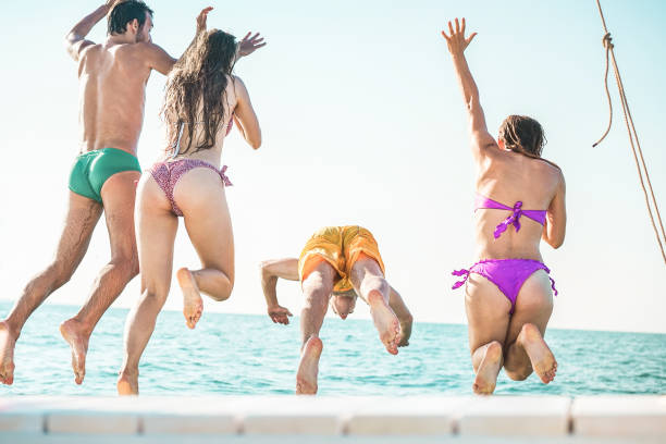 Crazy friends jumping off the boat into the ocean - Young happy people having fun diving into the sea - Travel, tropical, summer and concept - Focus on center guys - fotografia de stock